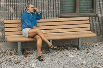 Woman sitting on tan bench