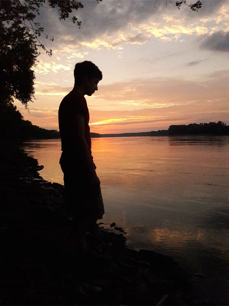 Front Cover - photo of a boy&#39s silhouette in front of the river at sunset