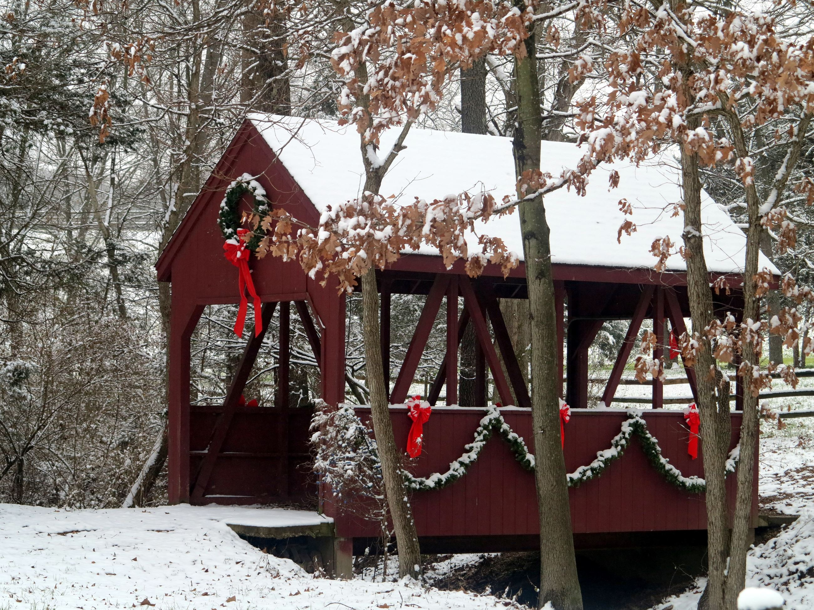 December 2017 Calendar image - covered bridge with red bows and garland in the snow
